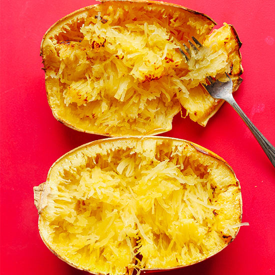 Fork resting in a baked and shredded spaghetti squash half