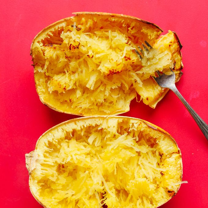 Using a fork to create spaghetti squash noodles from a baked squash