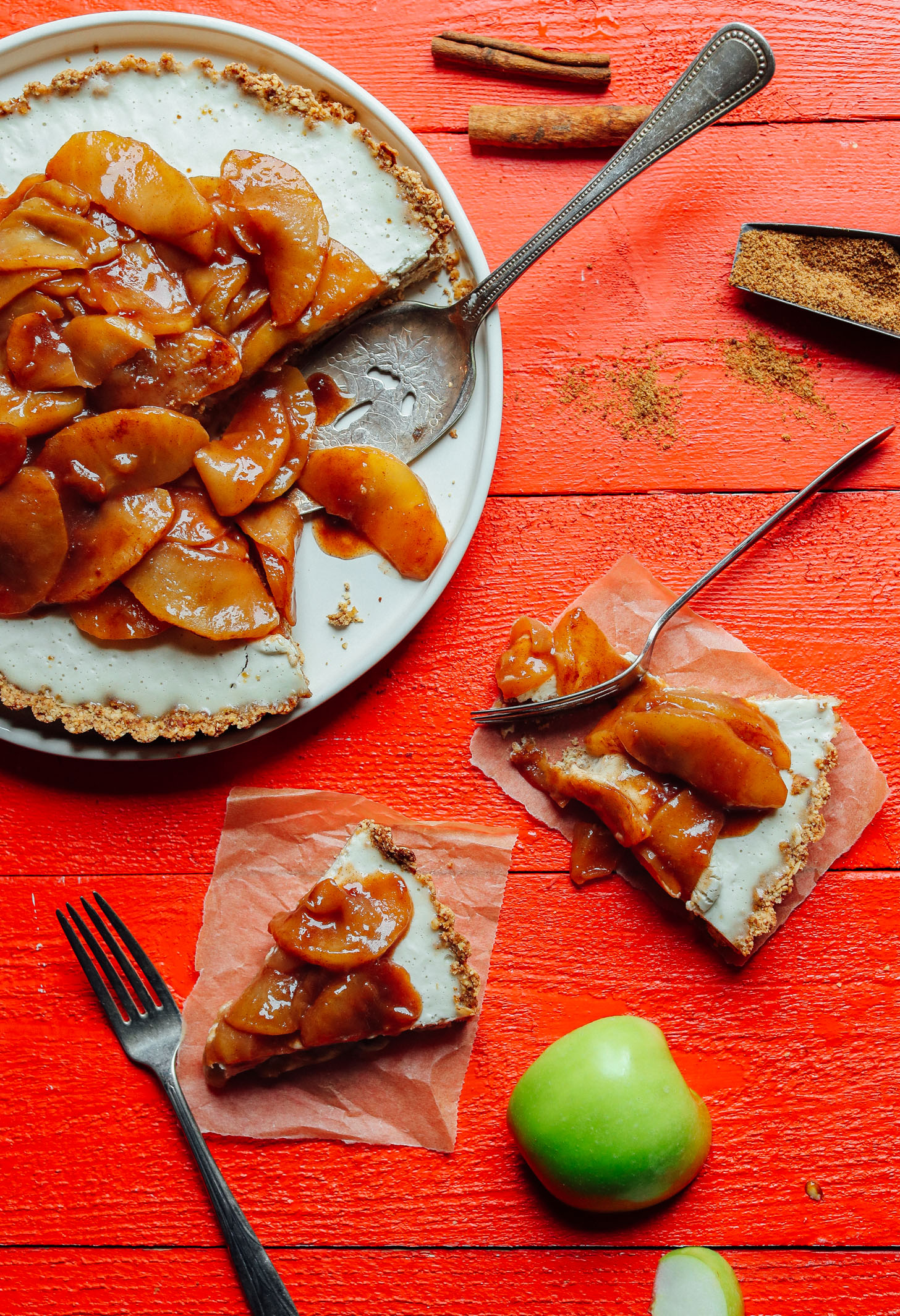 Slices of Caramel Apple Tart on parchment paper squares beside the whole dessert
