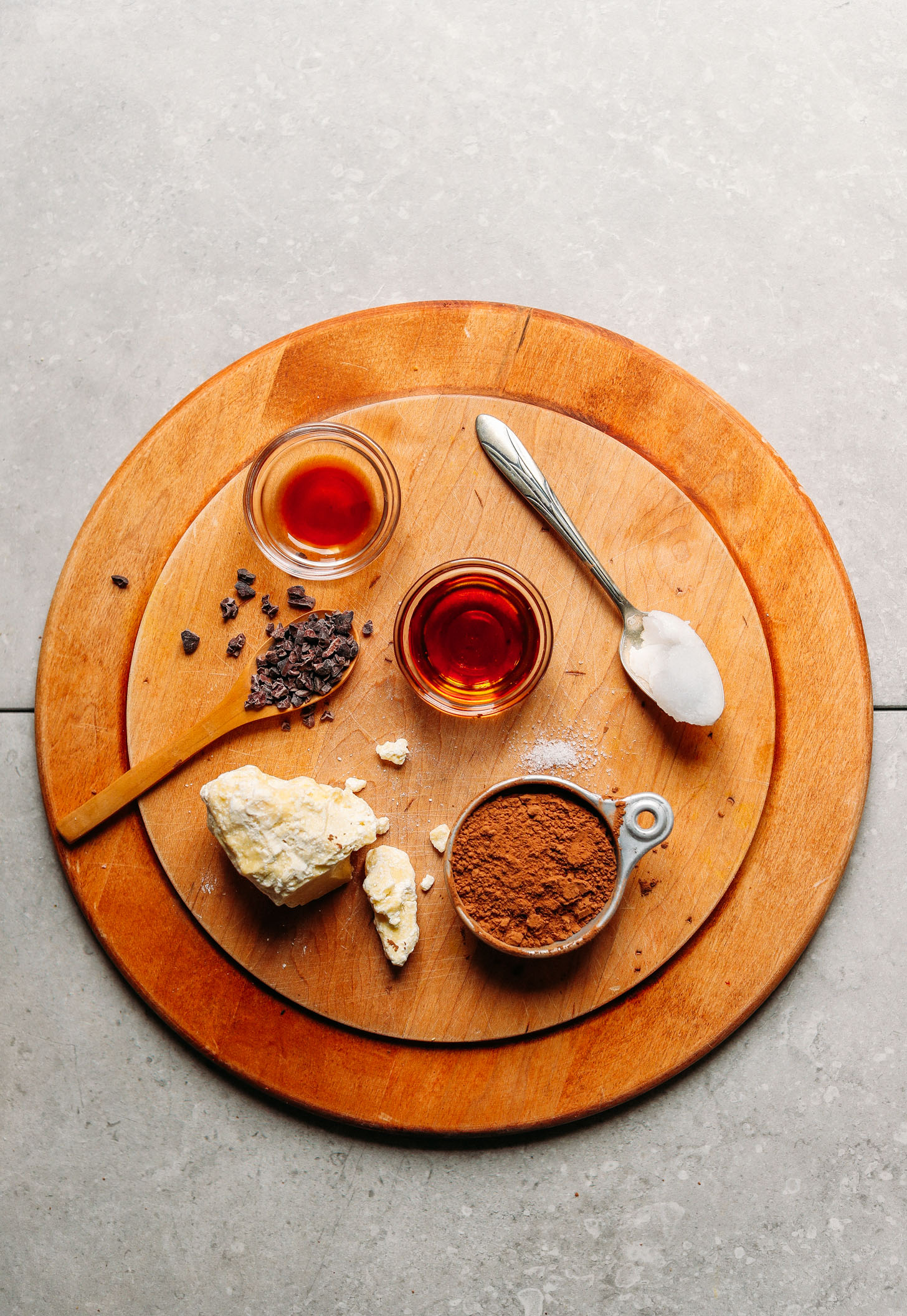 Wood platter featuring cocoa butter, cacao powder, coconut oil, maple syrup, salt, vanilla extract, and cacao nibs for making DIY Vegan Dark Chocolate