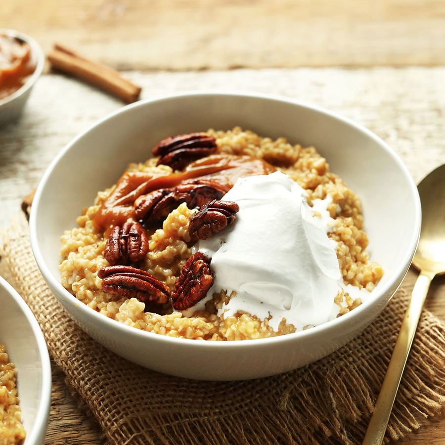 Bowl of Pumpkin Pie Oats topped with pecans and coconut whip for our roundup of Easy Vegan Breakfast Ideas