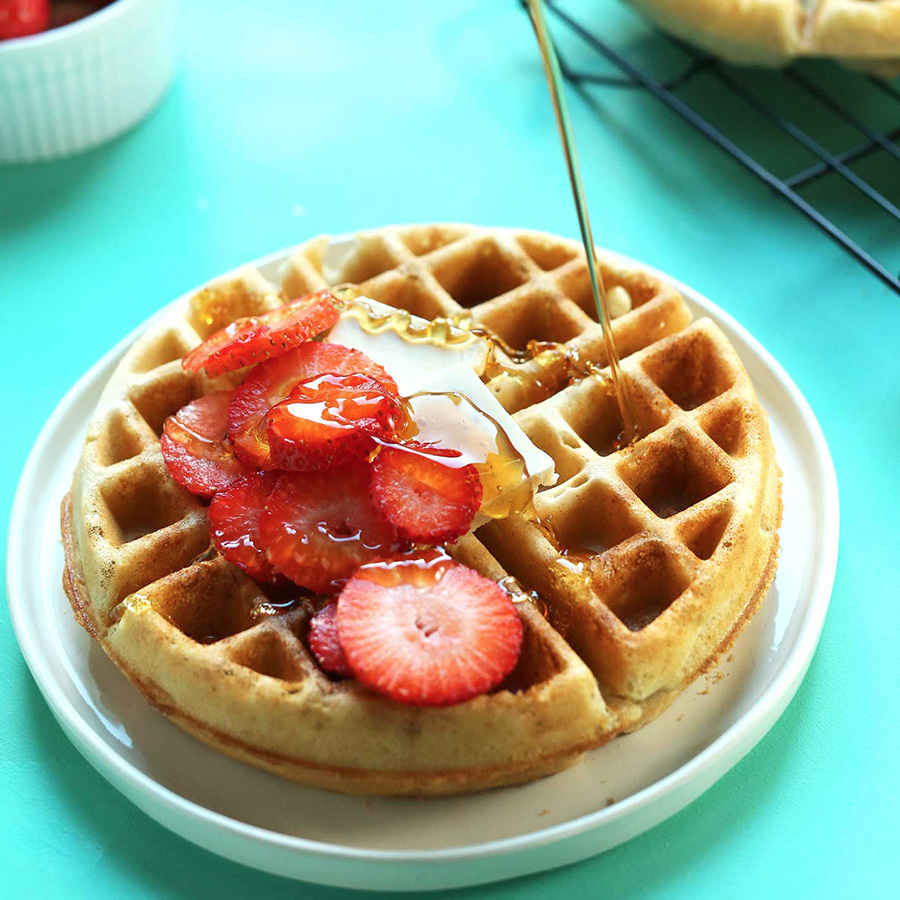 Pouring syrup onto a stack of our gluten-free waffles as part of our Easy Vegan Breakfast Ideas roundup