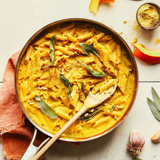 Pan of Vegan Pumpkin Mac 'n' Cheese topped with fresh sage leaves