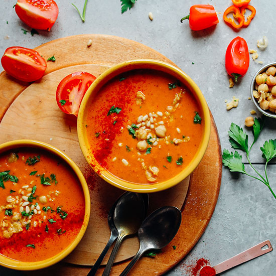 Two bowls of Romesco Soup surrounded by ingredients used to make it