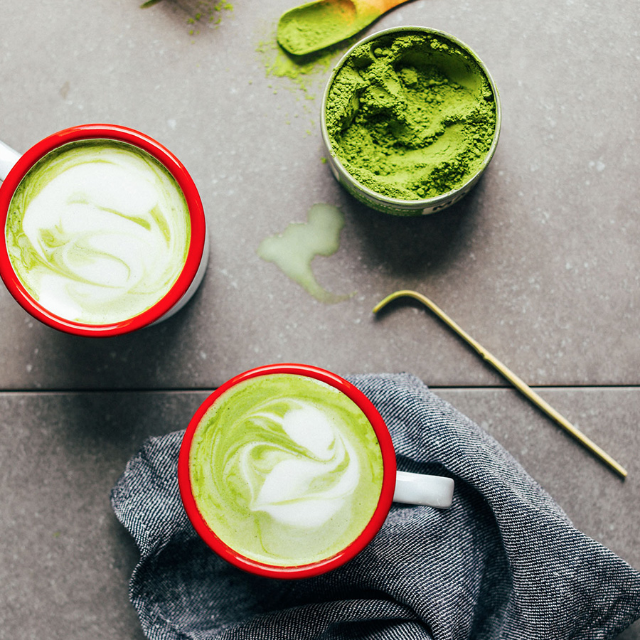 Mugs of matcha and tin of matcha powder as part of our roundup of Easy Vegan Breakfast Recipes