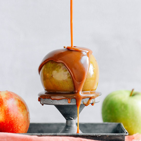 Drizzling Vegan Caramel Sauce onto an apple perched on a metal stand