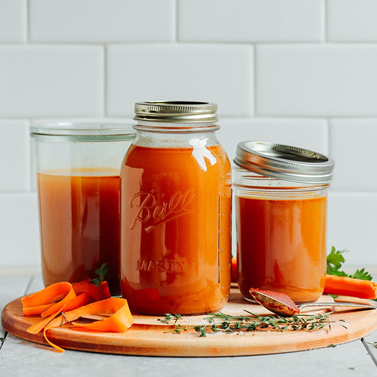 Jars of homemade Easy 1-Pot Vegetable Broth on a cutting board with tomato paste, carrots, and herbs
