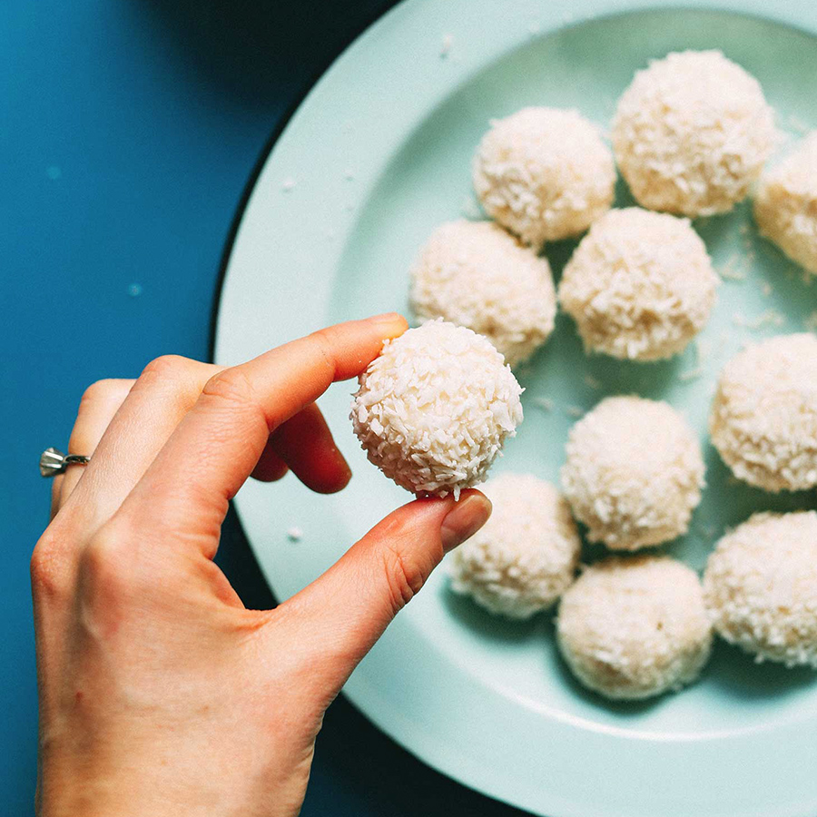 Holding up a Vegan White Chocolate Truffle coated in shredded coconut