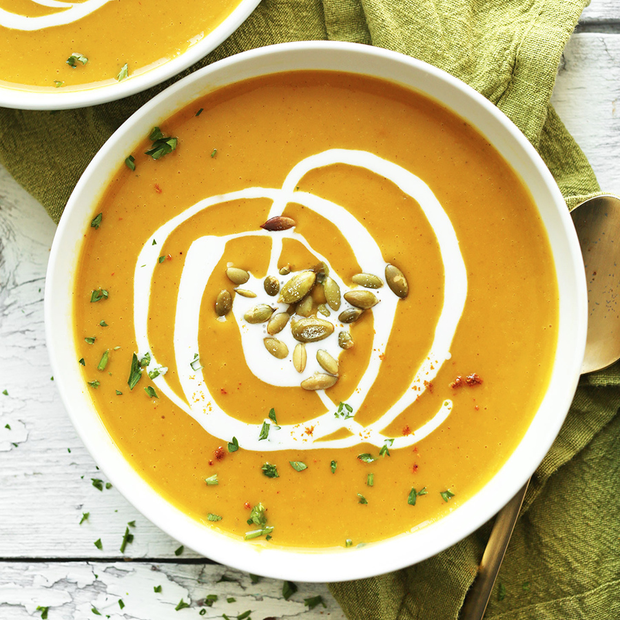 Big bowl of our Curried Butternut Squash Soup topped with coconut milk and pepitas