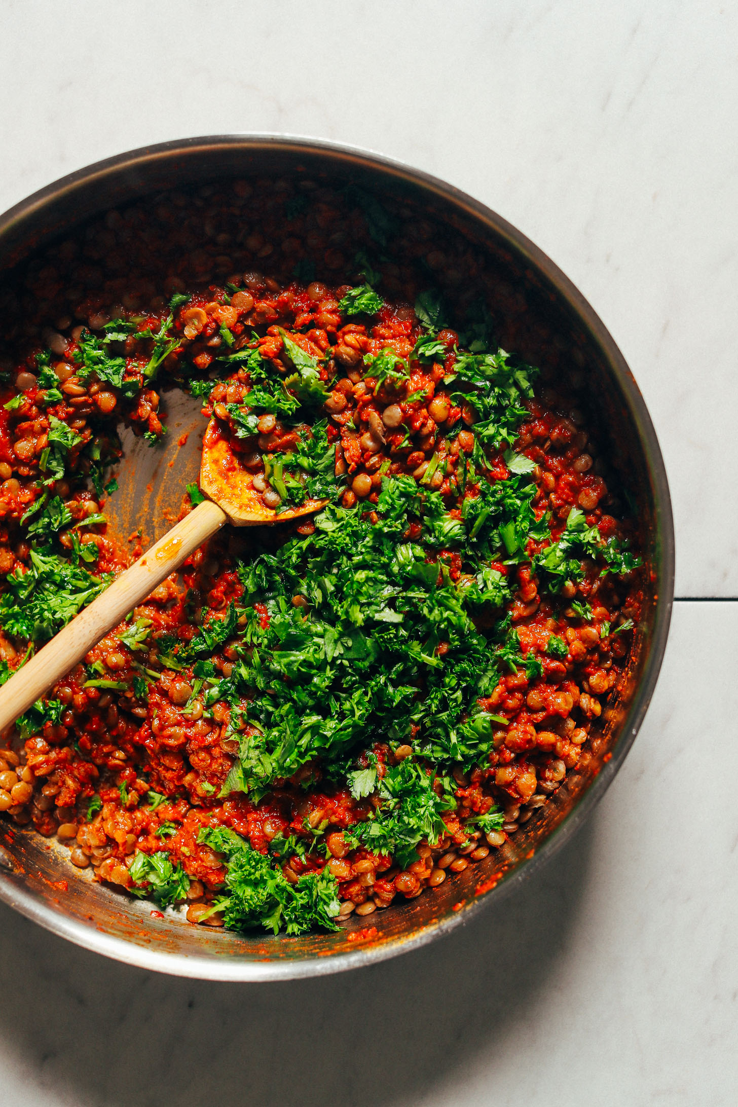 Large saute pan with Moroccan-Spiced Lentils garnished with fresh parsley and cilantro
