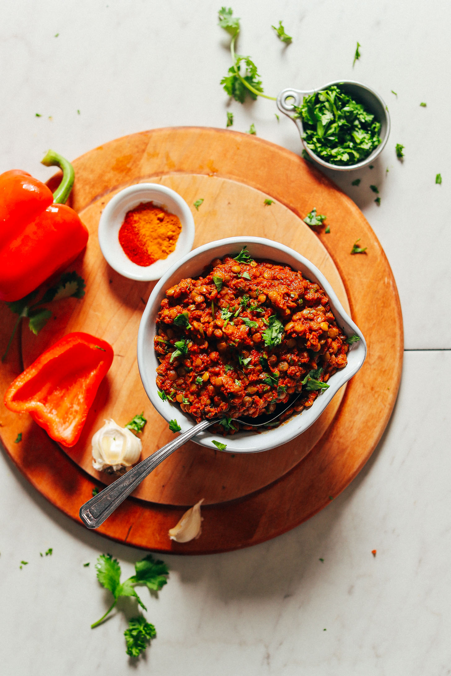 Big bowl of Moroccan Spiced Lentils surrounded by red bell pepper, garlic, fresh parsley, cilantro, and spices