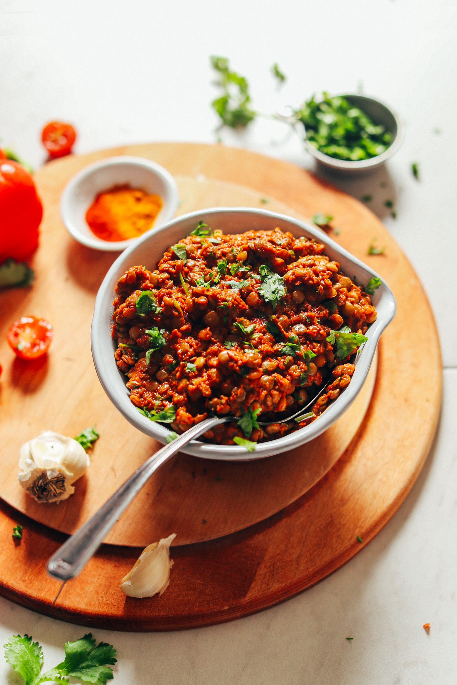 Close up shot of a big bowl of Moroccan-Spiced Lentils on a wood cutting board with fresh ingredients