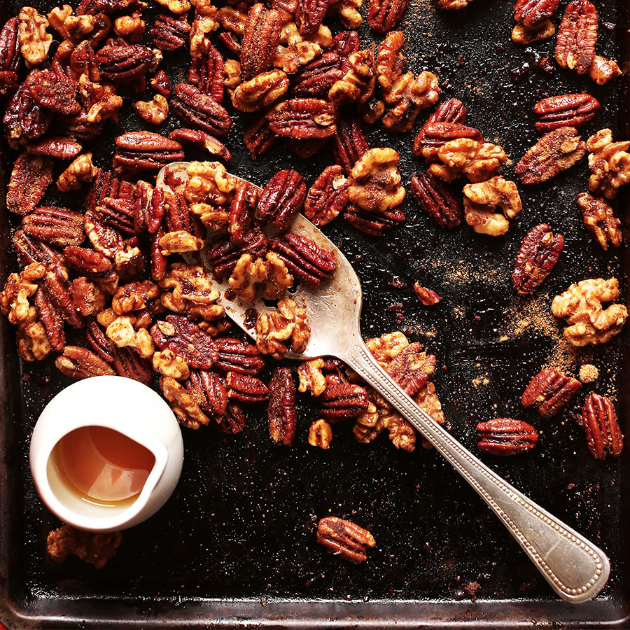 Maple syrup on a tray of Roasted Candied Pecans and Walnuts