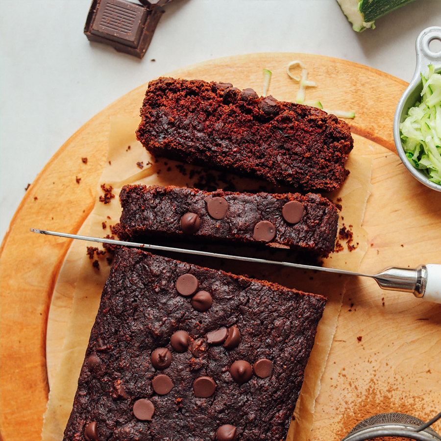 Slicing into a loaf of Vegan Chocolate Chocolate Chip Zucchini Bread