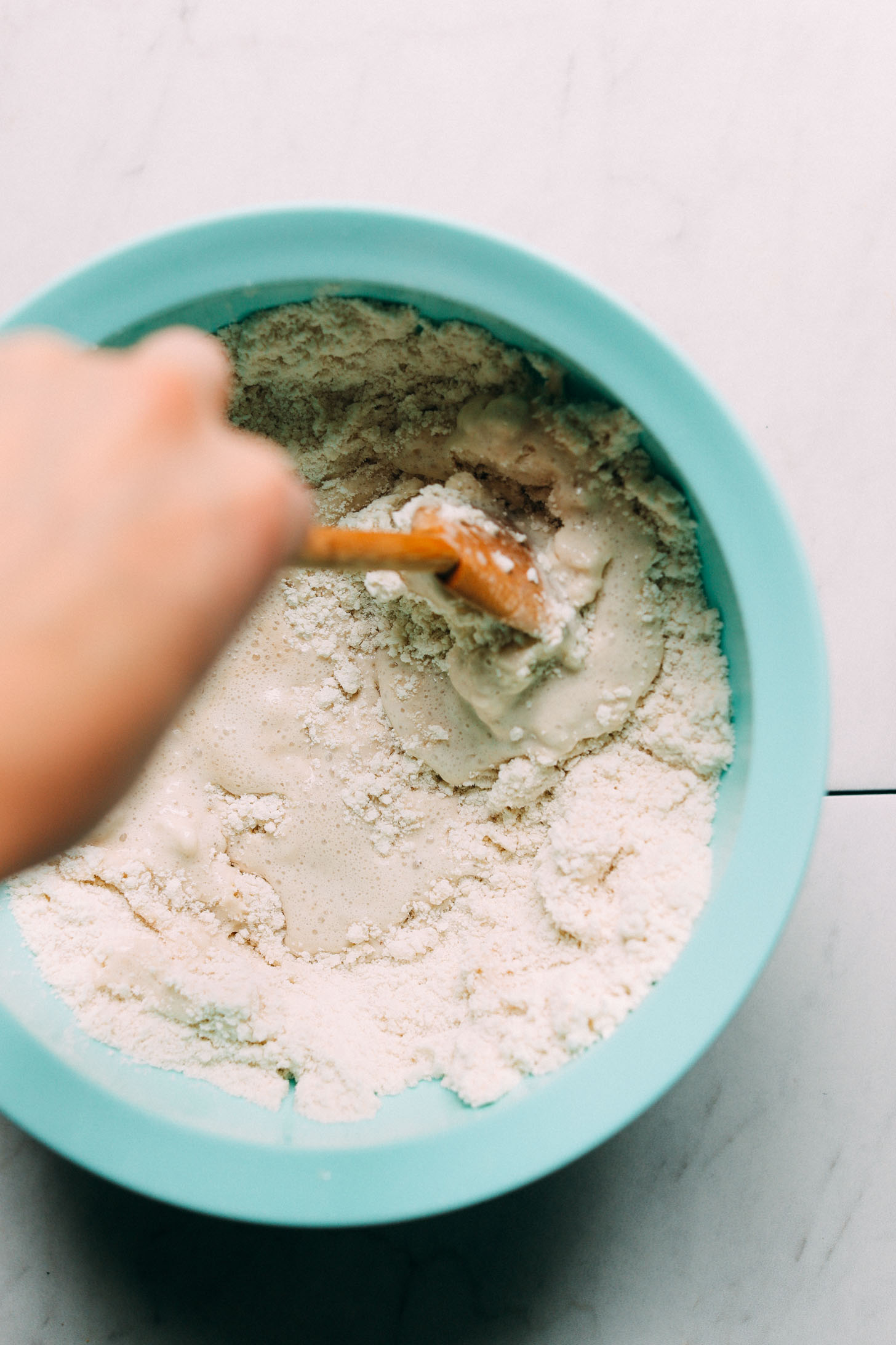 Stirring wet ingredients into dry ingredients with a wooden spoon