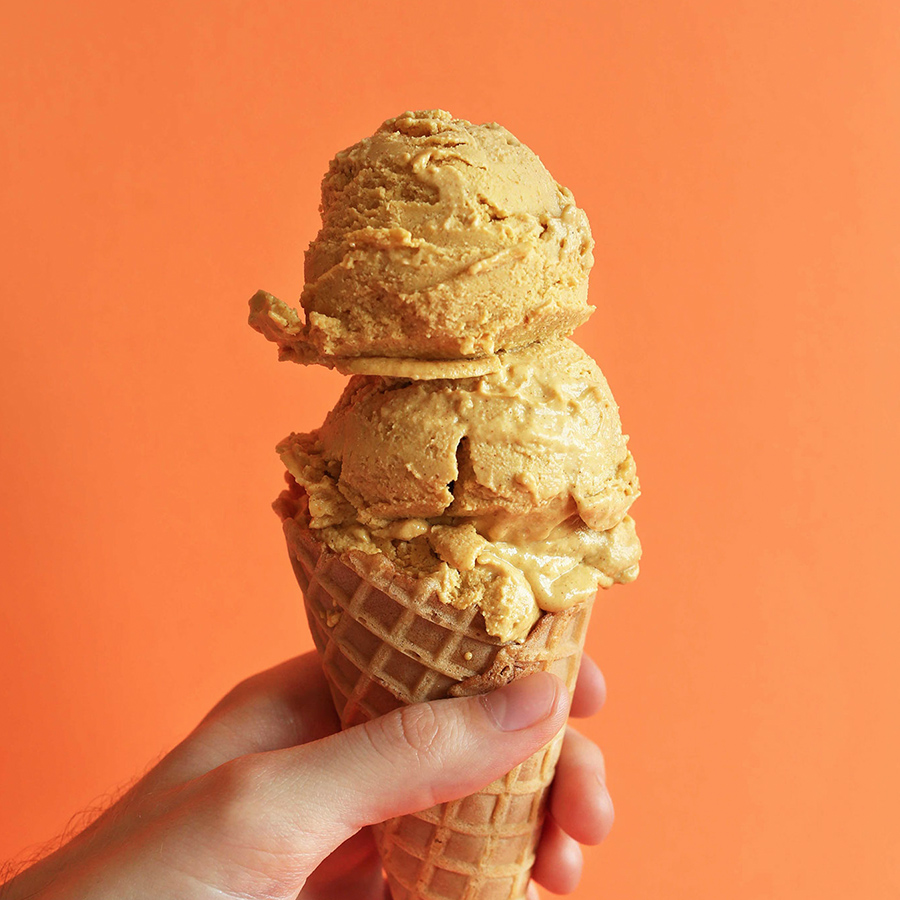 Holding an ice cream cone filled with two scoops of our homemade vegan Pumpkin Pie Ice Cream