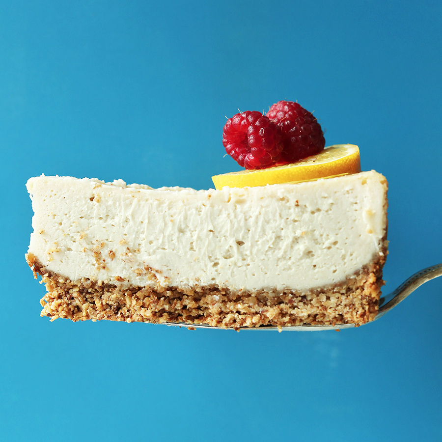 Holding up a slice of our simple Vegan Gluten-Free Cheesecake topped with fresh raspberries and lemon