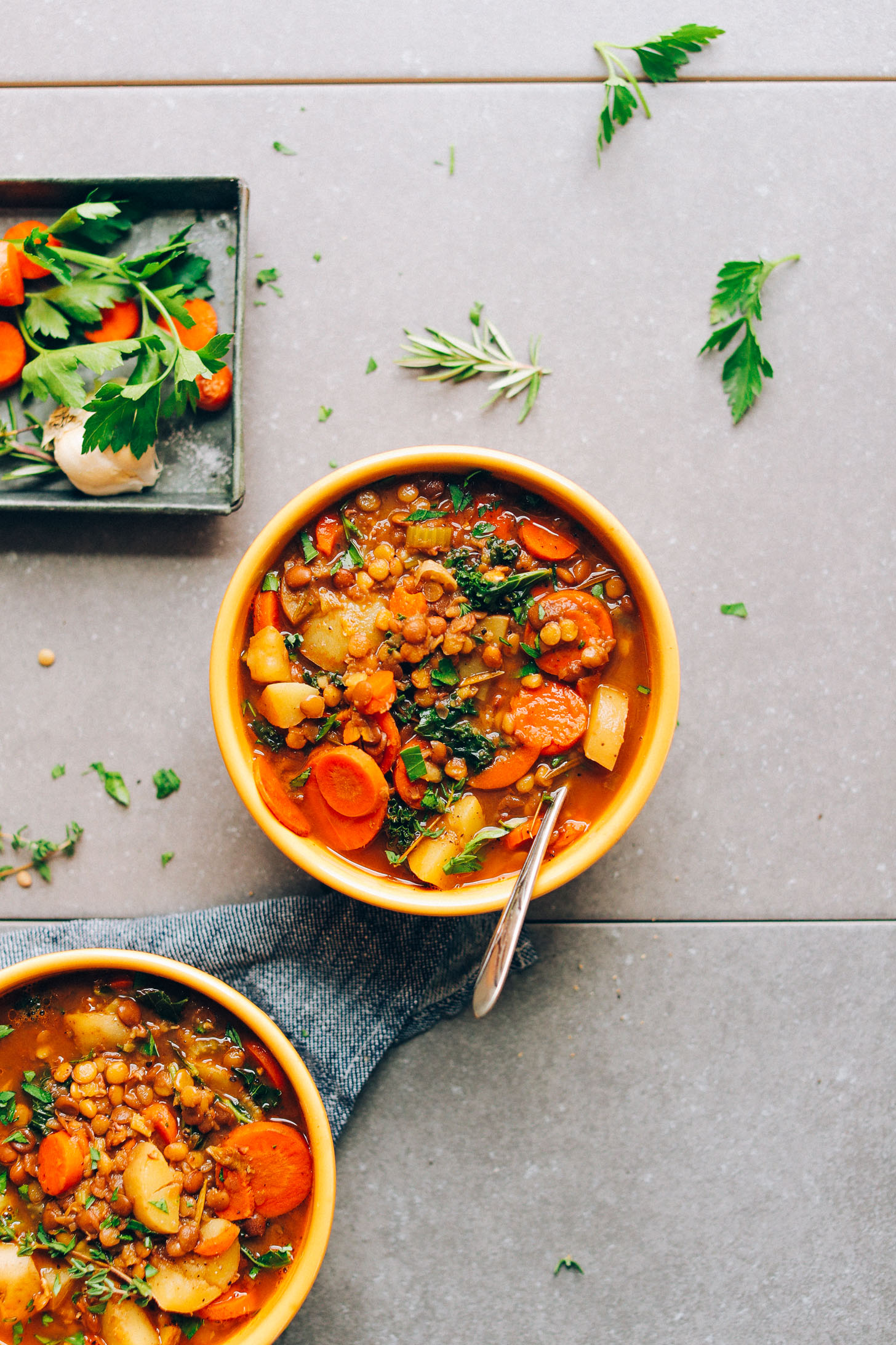 Overhead shot of two bowls of Everyday Lentil Soup with fresh herbs