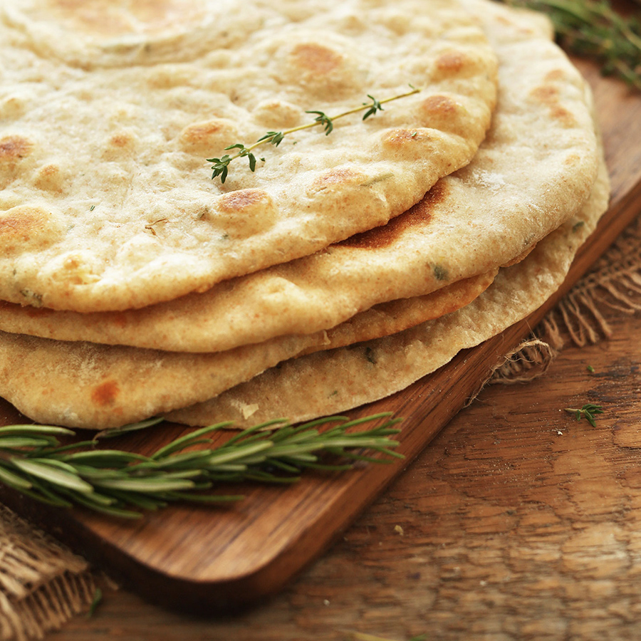 Cutting board with a stack of our healthy Vegan Flatbreads made with garlic and herbs