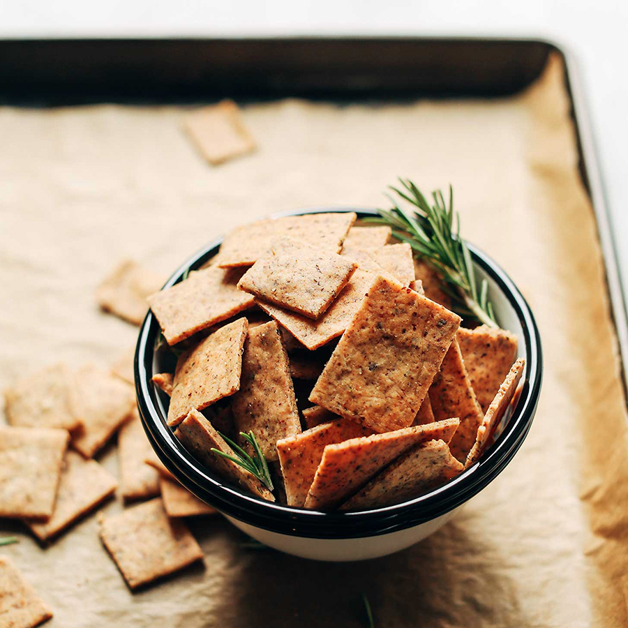 Bowl of homemade Gluten-Free Crackers in a bowl with sprigs of fresh rosemary