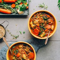 Bowls of Everyday Vegan Lentil Soup beside a tray of vegetables