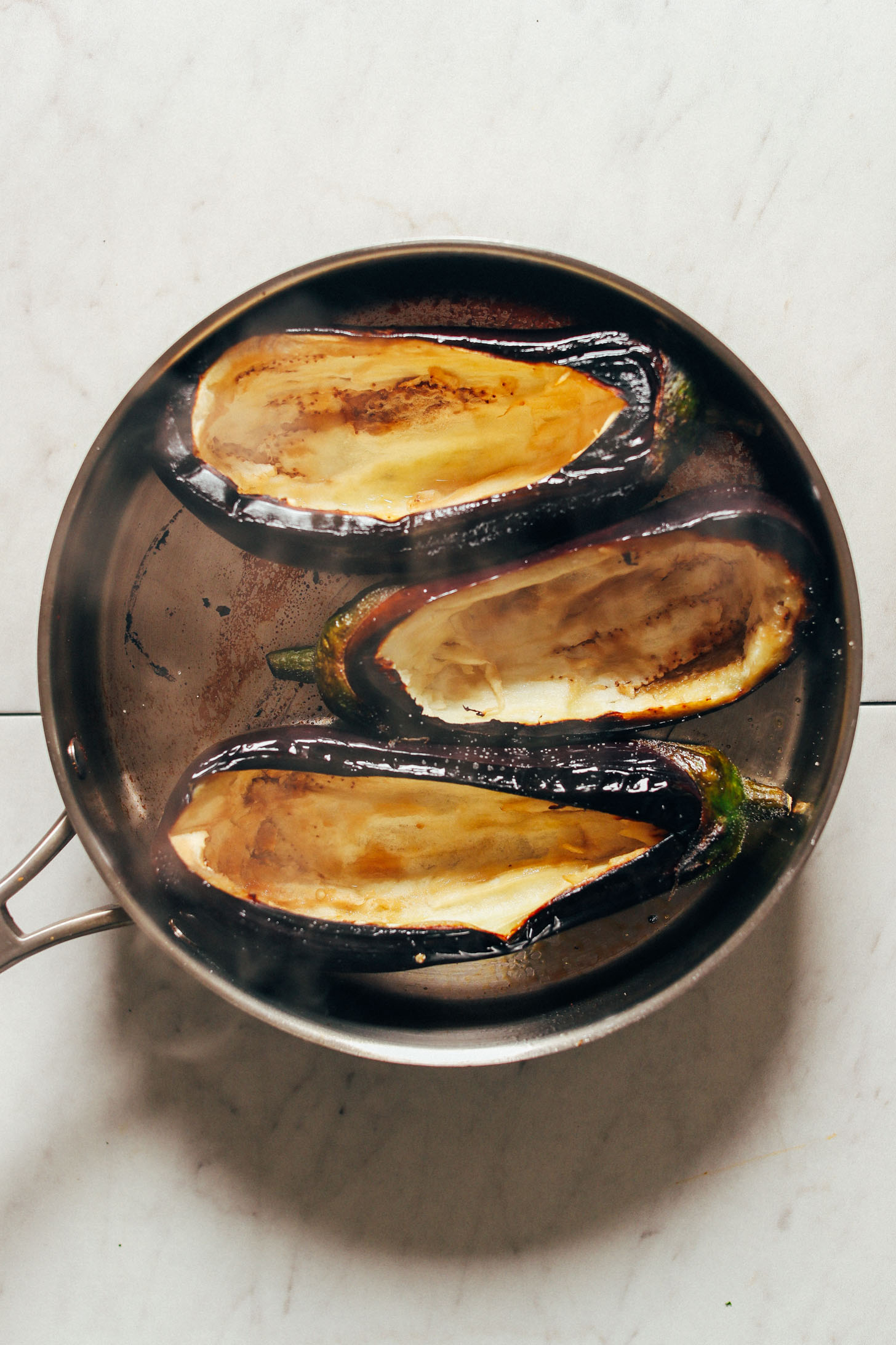 Nicely charred eggplants in a large saute pan