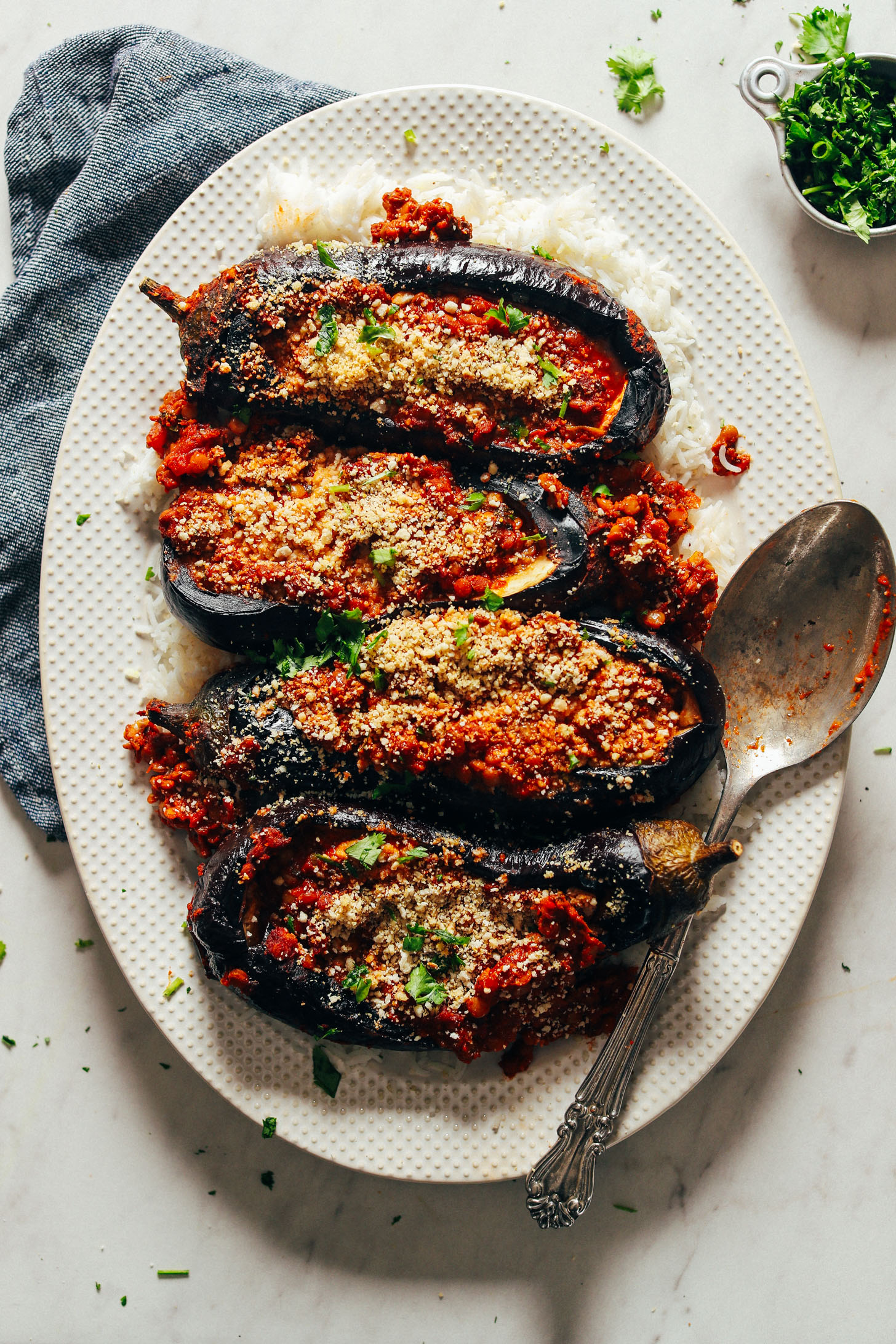 A platter full of Moroccan Lentil-Stuffed Eggplant on a bed of basmati rice for the perfect plant-based meal
