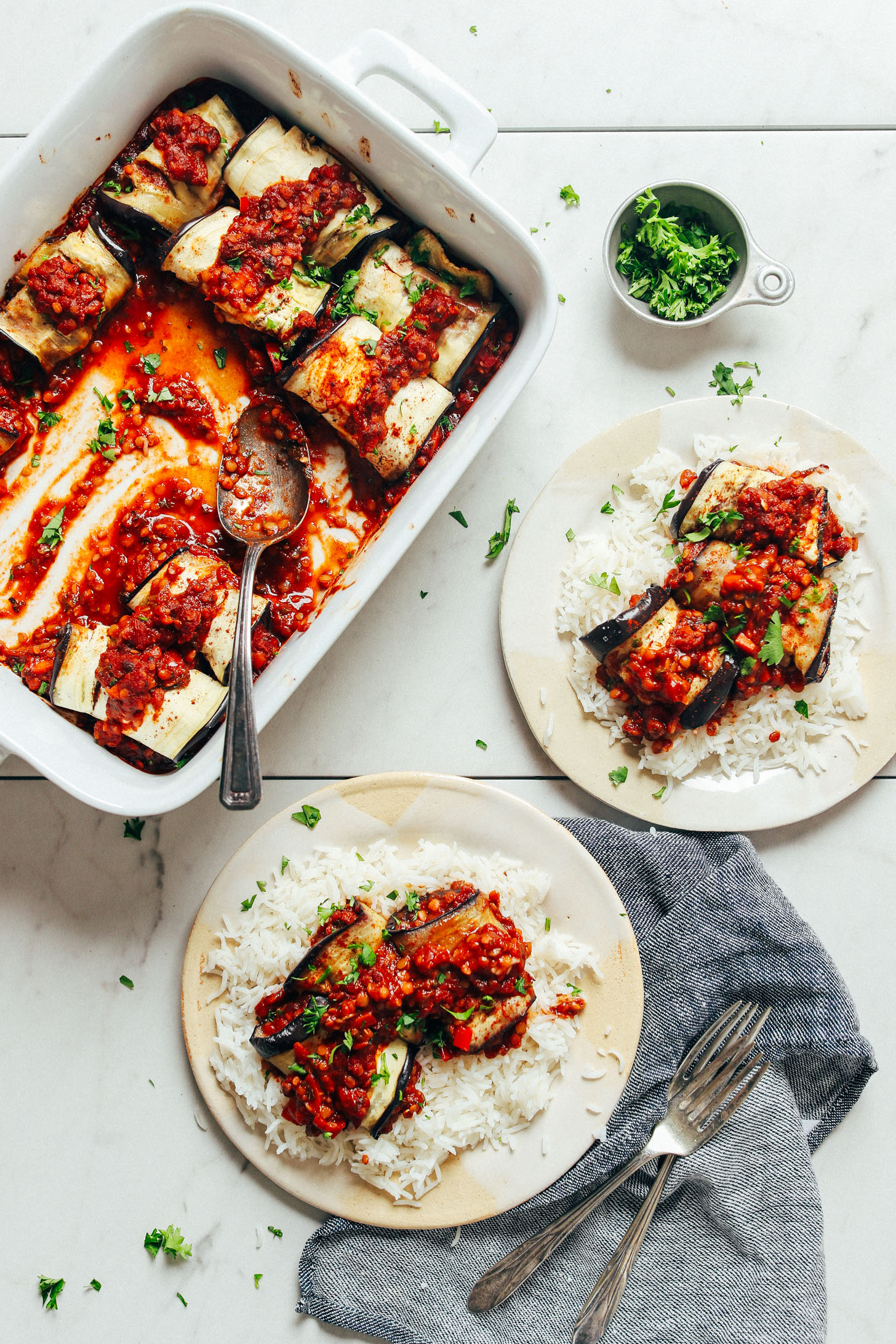 Eggplant rolls in a baking dish and on dinner plates over a bed of rice