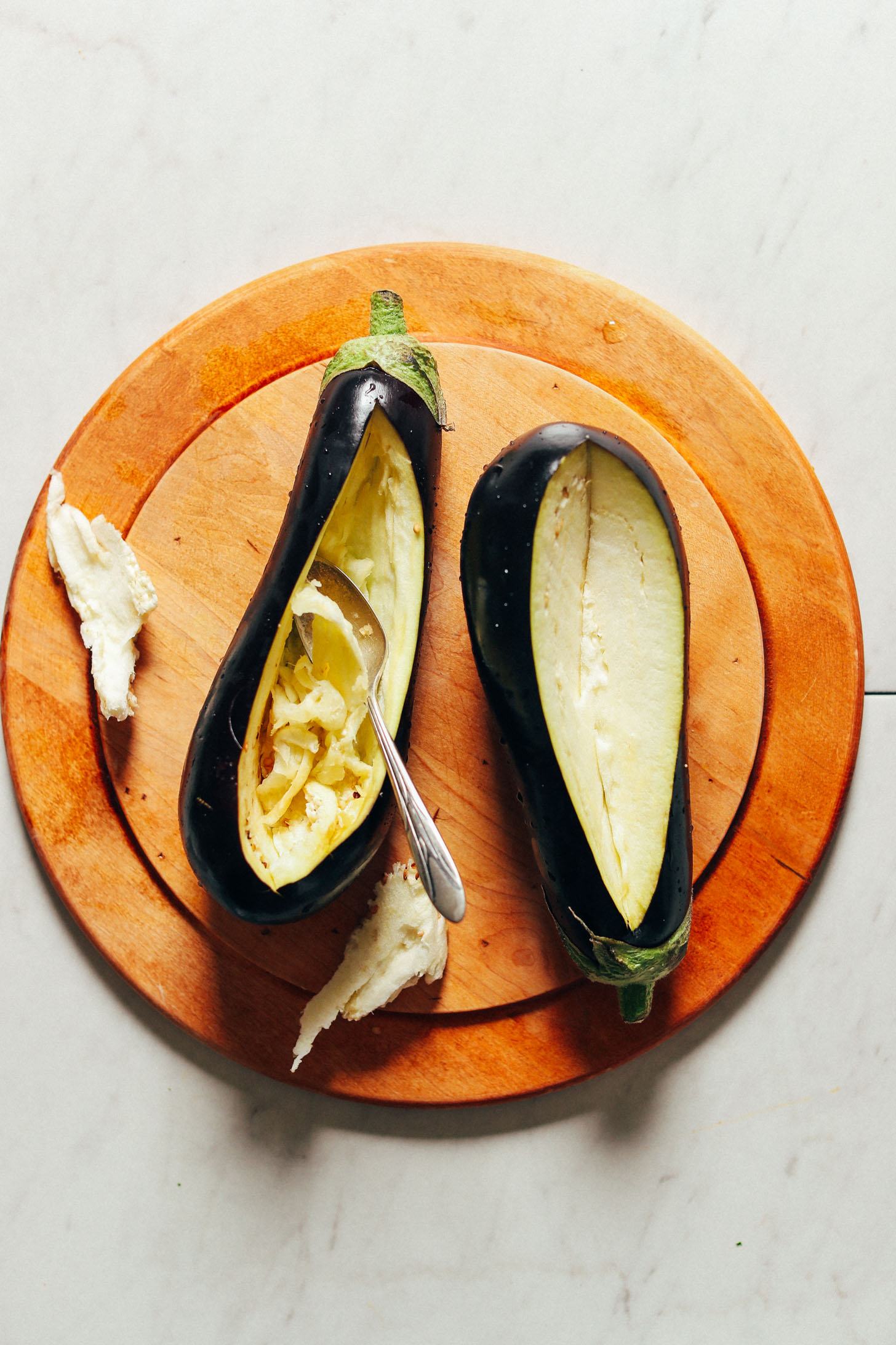 Scooping out flesh from eggplants for making Moroccan Lentil-Stuffed Eggplant
