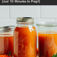 Jars of homemade vegetable broth on a cutting board