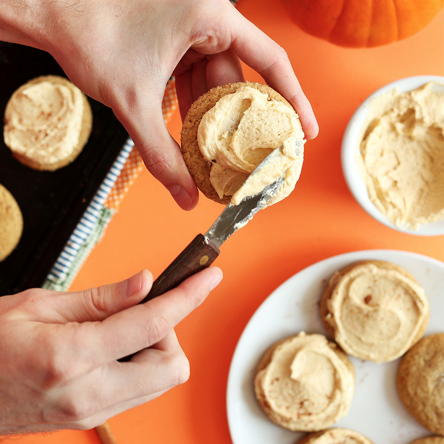 Using a knife to spread icing onto a Vegan Pumpkin Sugar Cookie