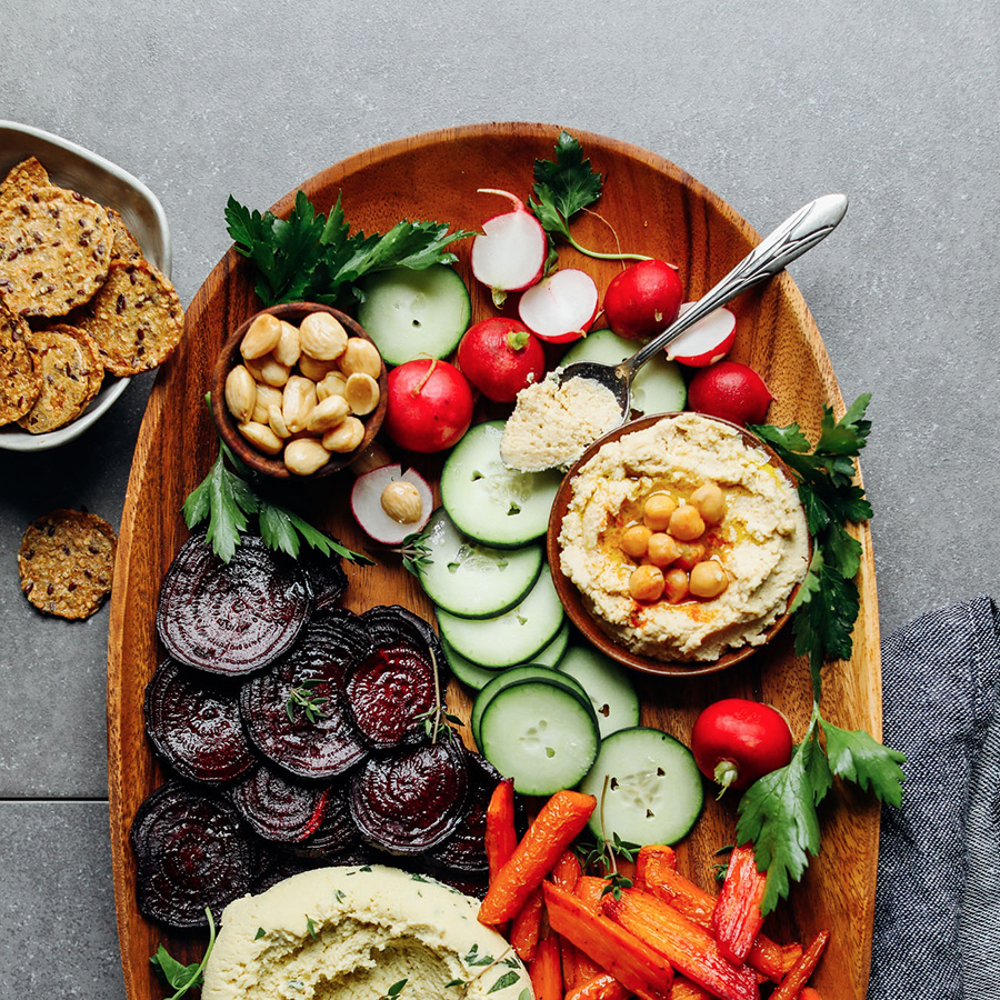 Wood platter filled with hummus, vegetables, almonds, crackers, and Macadamia Nut Cheese Crudite