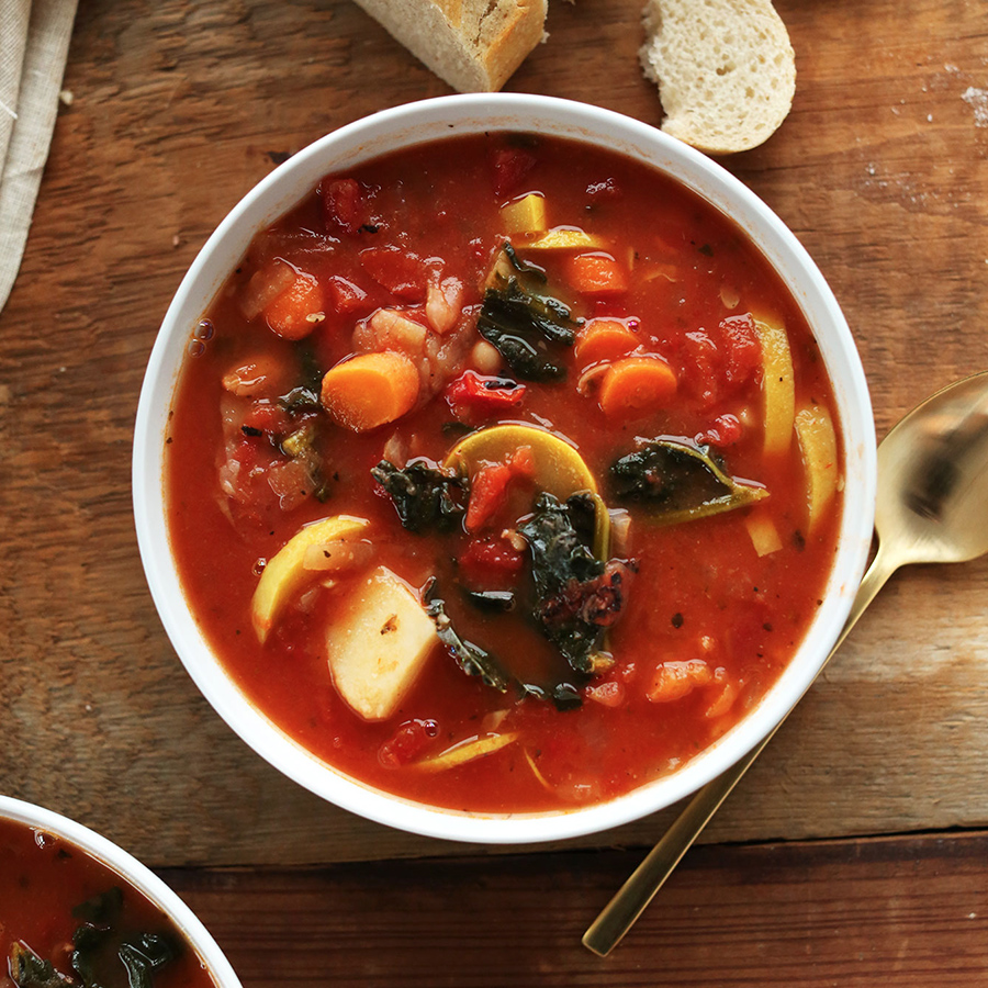 Stirring a pot of Soul-Warming Vegan Stew made with potatoes, kale, and tomatoes