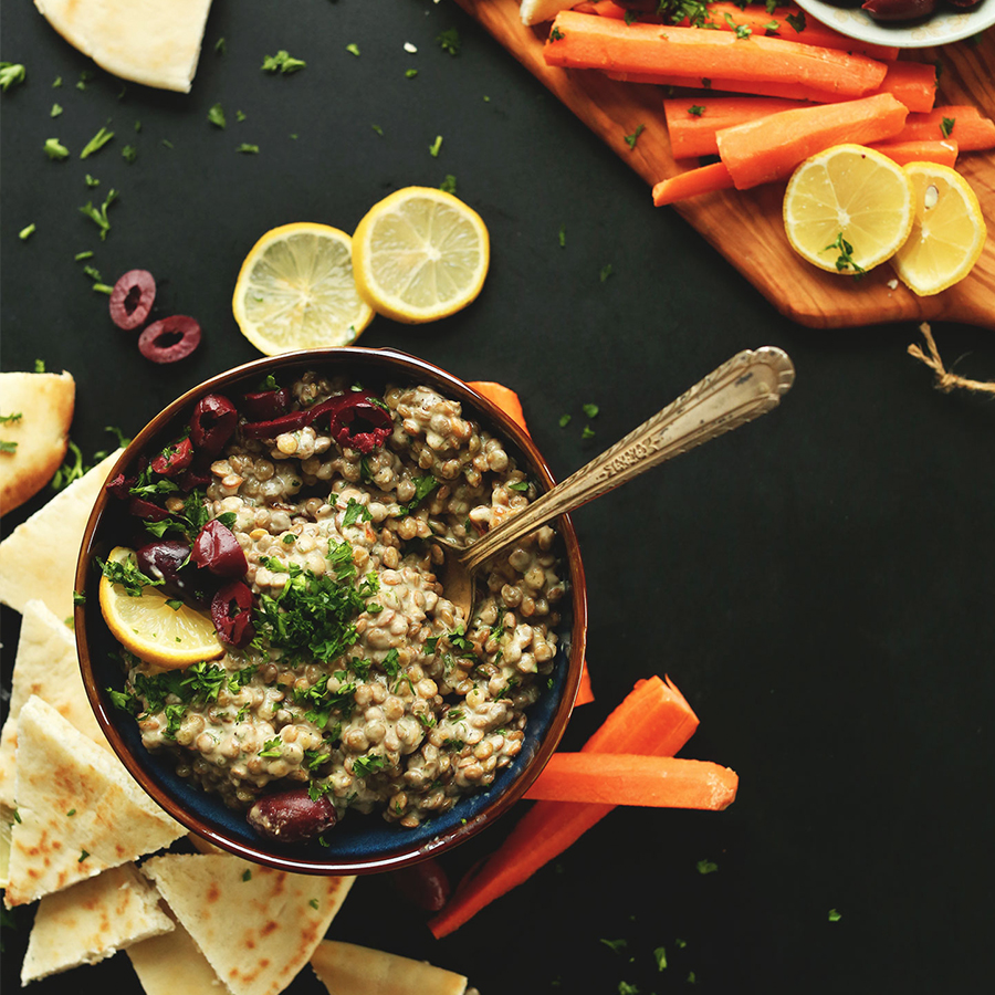 Spoon resting in a bowl of Mediterranean Lentil Dip topped with parsley and kalamata olives