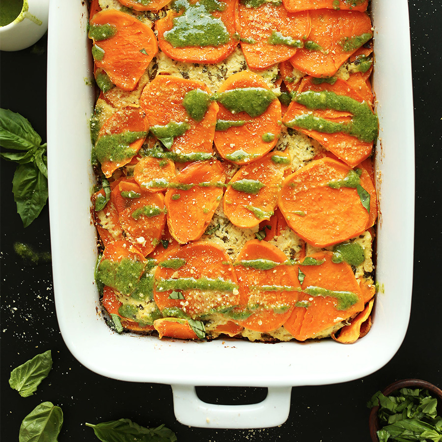 Ceramic baking pan filled with a batch of our Vegan Sweet Potato Lasagna recipe topped with basil pesto drizzle