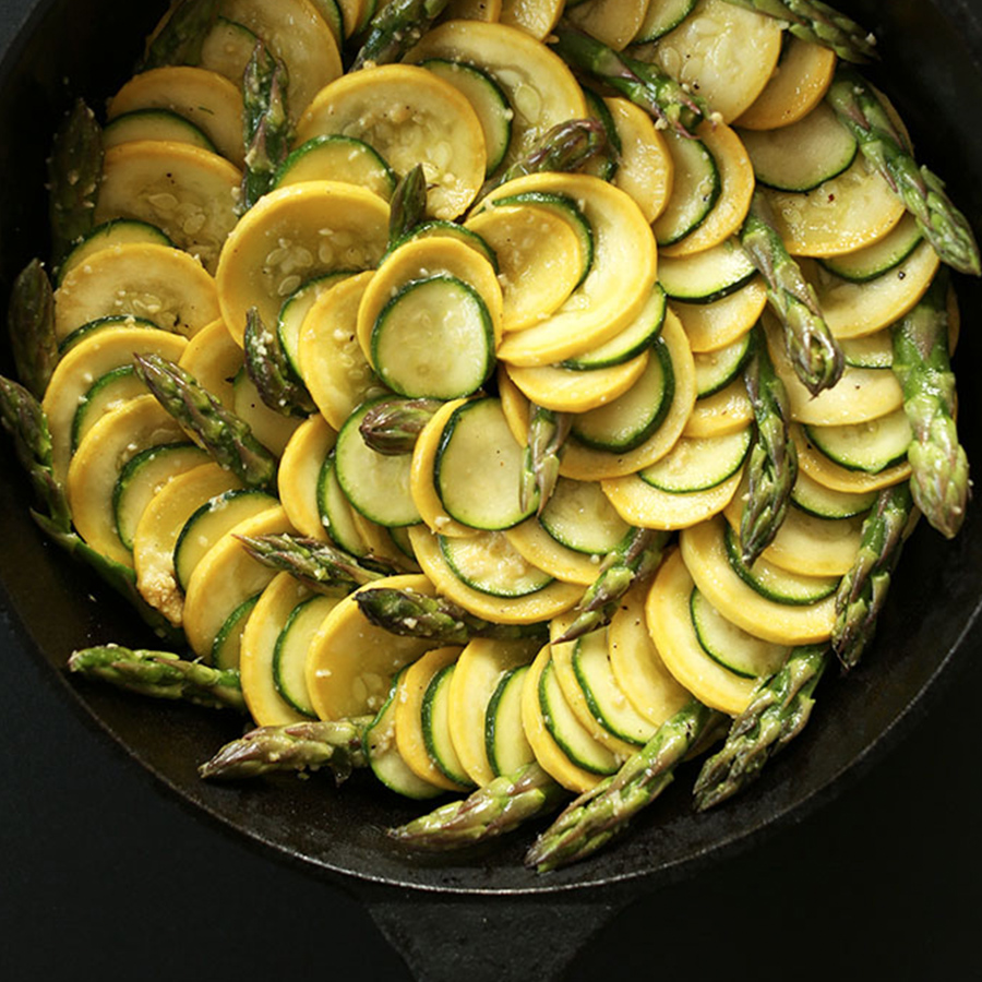 Cast-iron skillet filled with Zucchini Asparagus Gratin arranged in a beautiful spiral design