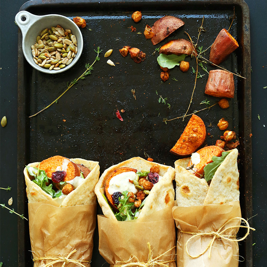 Baking sheet with roasted sweet potatoes, pepitas, and three wraps to use up Thanksgiving leftovers