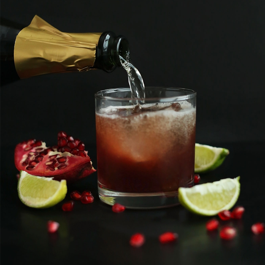 Pouring sparkling wine into a glass to make our festive Pomegranate Margaritas