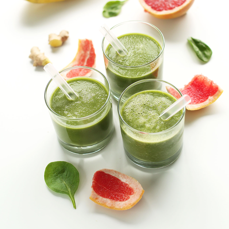 Three small glasses of our Grapefruit Green Smoothie recipe surrounded by ingredients to make it