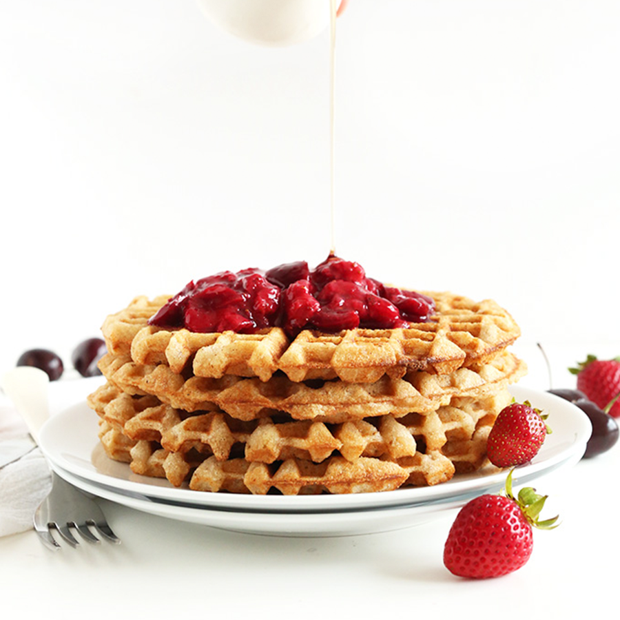 Drizzling maple syrup onto a stack of Vegan Gluten-Free Waffles with berry compote