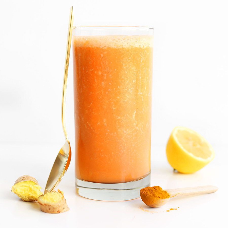 Spoon leaning on a tall glass filled with our Carrot Ginger Immune Boosting Smoothie recipe