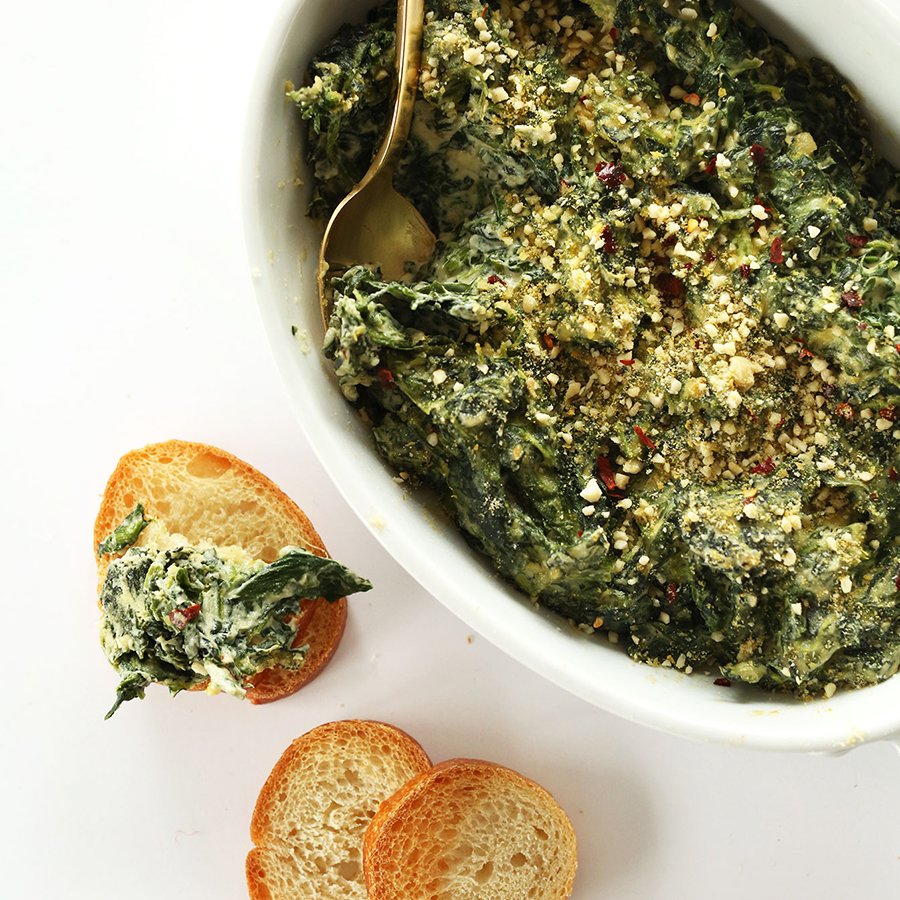 Slices of bread and a bowl of Creamy Kale and Spinach Dip for a vegan appetizer