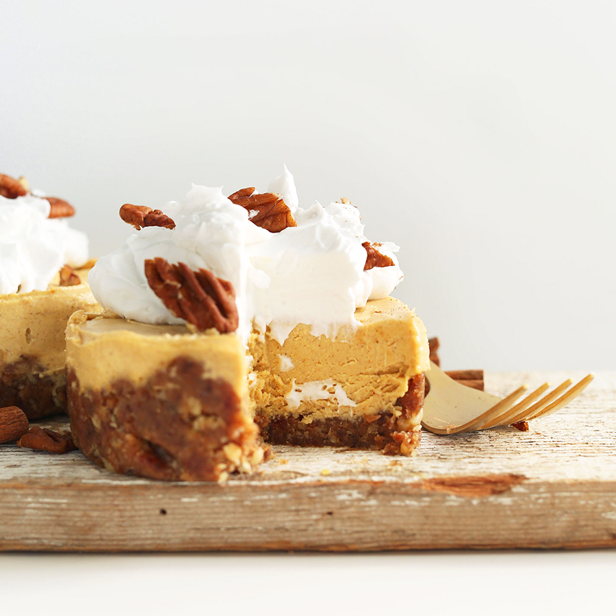 A mini Vegan Pumpkin Cheesecake topped with coconut whipped cream and pecans