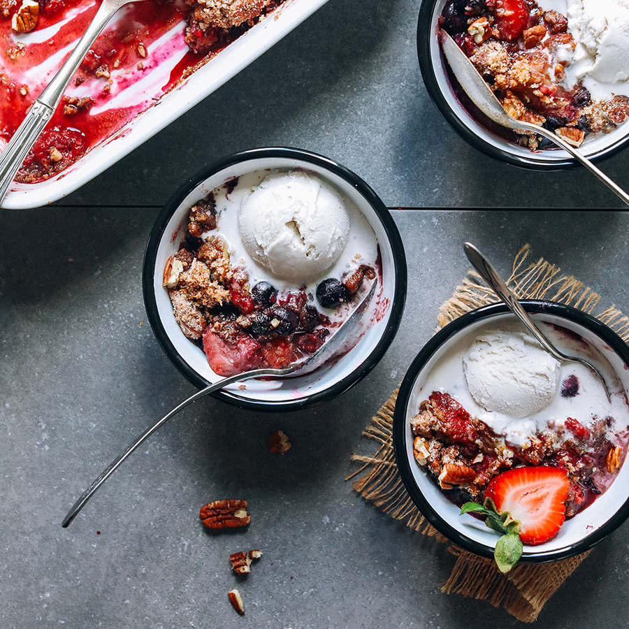 Three bowls and pan of Grain-Free Berry Crisp topped with vegan ice cream