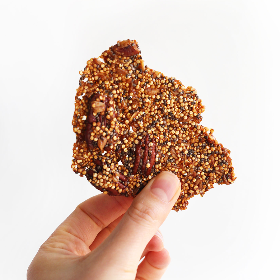 Holding up a piece of Quinoa Brittle for a dessert loaded with protein