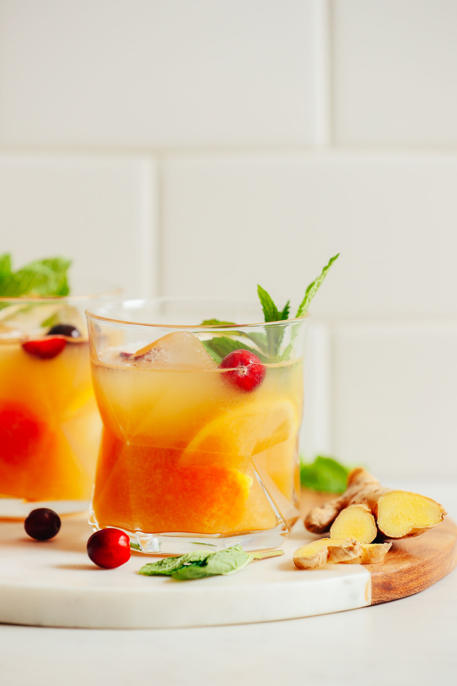 Close up shot of an Orange Whiskey Ginger with Mint and garnished with fresh cranberries