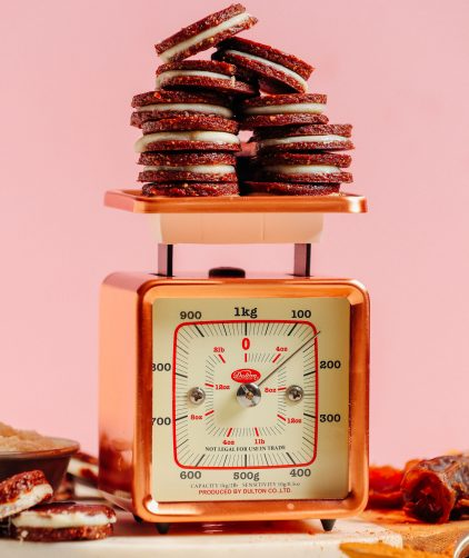 A vintage gold scale holding several gluten-free Raw Oreo Cookies