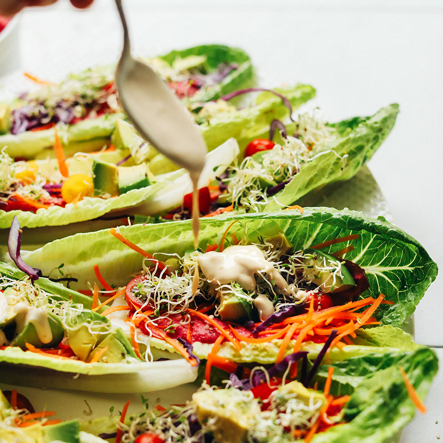 Drizzling sauce onto Raw Romaine Taco Boats filled with fresh vegetables