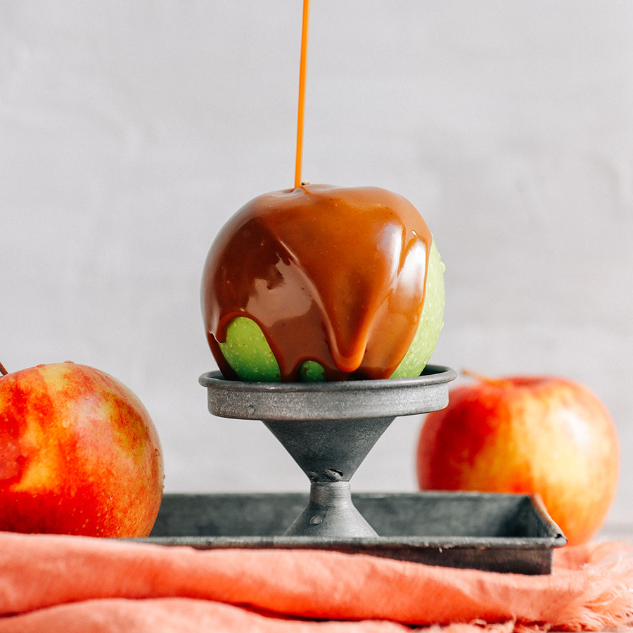 Drizzling homemade Vegan Caramel Sauce onto a granny smith apple