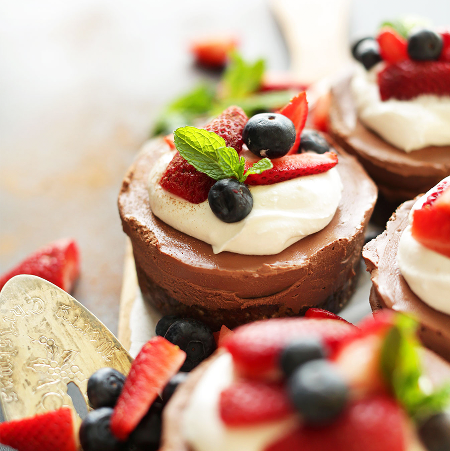 Platter of mini Vegan Chocolate Cheesecakes topped with coconut whipped cream, fresh berries, and mint